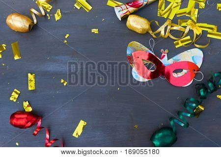 Masquerade confetti and masks frame with copy space on dark wooden background