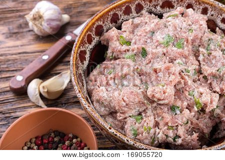 Grind the meat with spices in a bowl on a wooden board