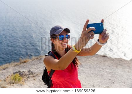 Young woman standing by sea on hill photographs herself