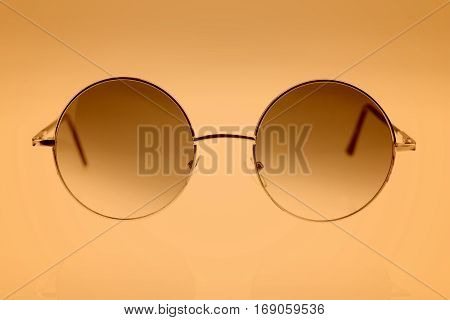 Close up of eyeglasses on brown background