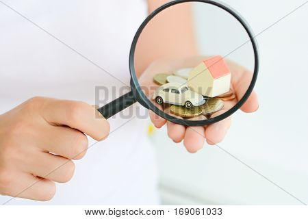 Magnifying glass in front of a toy house and a car suggesting family investments