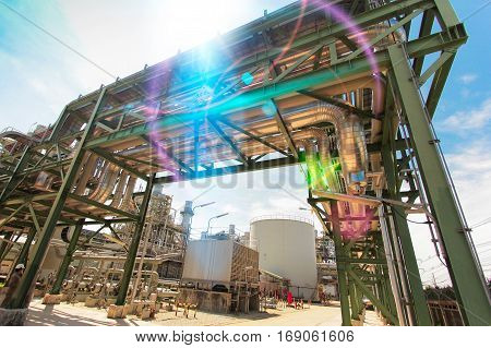 Equipment and pipeline in Industrial power plant with blue sky and lens flare