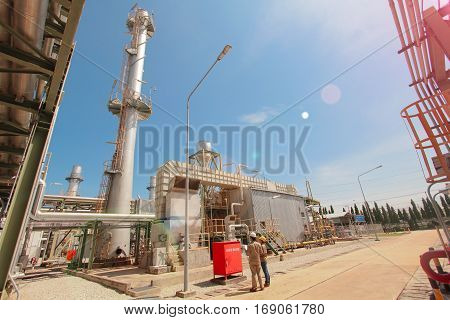 Two worker with gas terbine generator with blue sky
