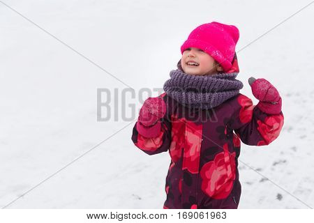 Small girl in winter overalls walks at park