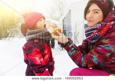 Mum feeds girl with bun on winter walk