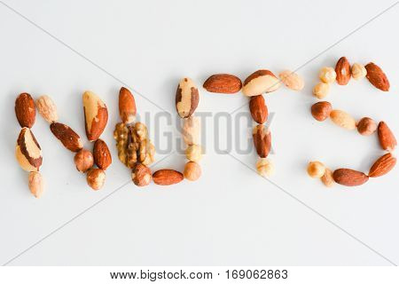 Nuts word spelled with nut mix isolated on white background