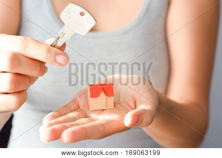Close-up of woman's hands holding a small model house and a key suggesting house acquisition or rental