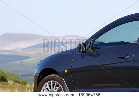 Car parked in the countryside in front of hills