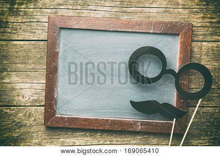 Blank chalkboard and fake glasses with mustache. Top view.