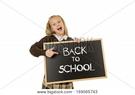 7 8 years old little beautiful blond schoolgirl smiling happy and cheerful holding and showing small blackboard with text back to school in end of holidays and education concept isolated white