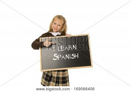 7 8 years old little beautiful blond schoolgirl smiling happy and cheerful holding and showing small blackboard with text I learn Spanish in language education concept isolated white