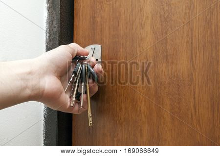 Close-up of a hand holding a bundle of different keys in key hole in wooden texture door.