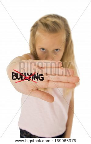 sweet and scared little schoolgirl showing the word bullying scratched written in her hand in the concept children bullied and abused in school isolated on white background