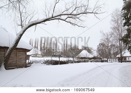 Ancient Ukrainian village covered in newly-fallen snow with authentic huts and fences
