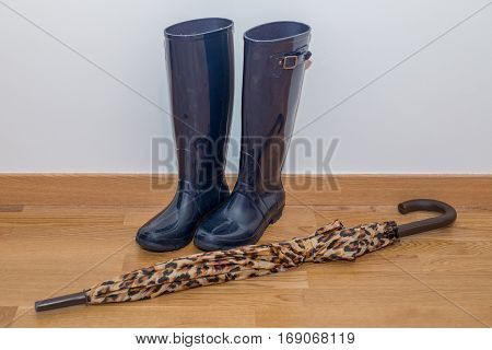 image of wet rubber boots with umbrella at the wall