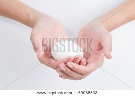 Woman hand holding White egg isolated on white background
