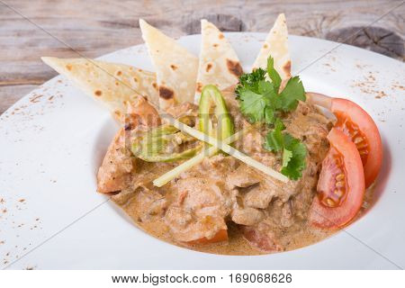 Traditional indian chicken masala dish served on a white plate