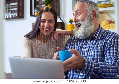 Extreme close-up of surprised smiling couple. Frankly speaking couple in front of the laptop. Sitting in the kitchen and working together