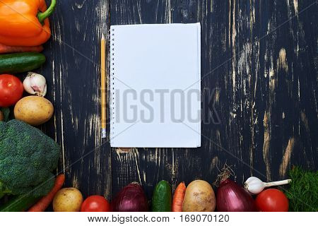 Overhead view of jotter with a pencil surrounded with a collection of homegrown vegetables. Shopping list or recipe. Place for the copy space