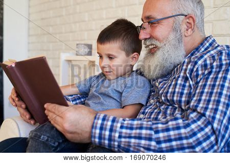 Mid shot of two person involving in reading. Grandfather supporting his kid to read a book while sitting in an armchair