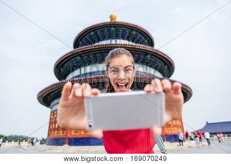Tourist taking goofy face funny selfie on travel. Happy young woman having fun with mobile phone at famous Beijing landmark. Temple of Heaven China travel.