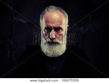 A mid shot of male peering into lens, having a grim expression. Man dressed in black knitted pullover