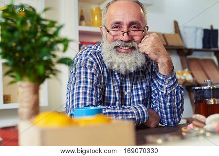Close-up of happy senior man looking at the camera. Sitting at the table and leaning his head on the hand. Side rack focus on mature, bearded man