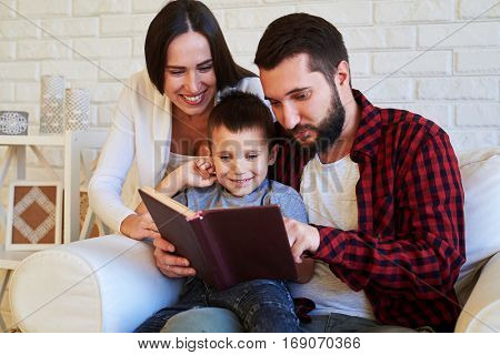 A mid shot of merry family looking at the book and smiling. A little boy sitting between his parents on the knees of his father