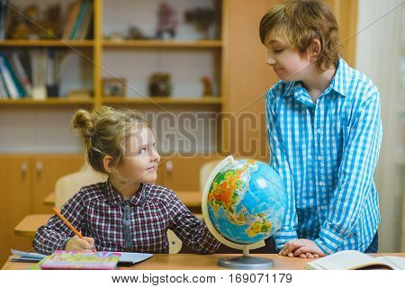 boy and girl on the geography lesson in school classroom. Educational concept.