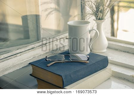 Getting an education - the road to knowledge. Reading books - the path to wisdom. Glasses, vase, cup, black and white books.