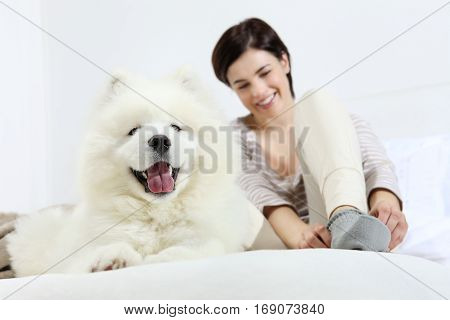 Smiling woman with pet dog lying in bed