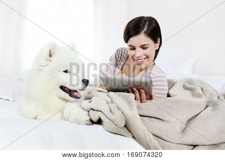 smiling woman with pet dog and tablet lying in bed
