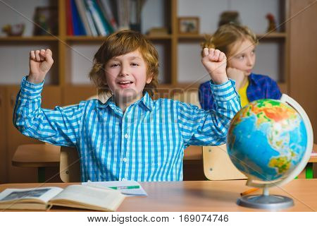 Happy smiling boy on the geography lesson in school classroom. Educational concept.