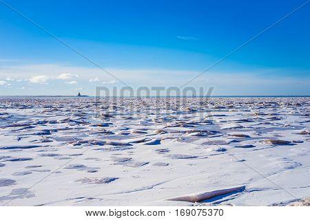 Ice of the shore along the Atlantic coast of Prince Edward Island, Canada.  Indian Head Lighthouse at the horizon.