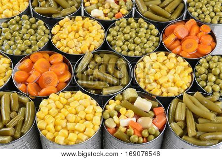 Closeup shot of cans of vegetables. Corn, Peas, Green beans, carrots in open cans filling the frame.