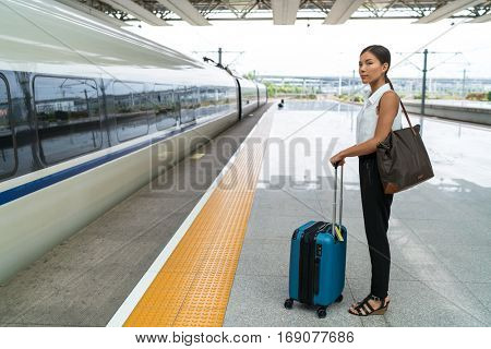 Asian traveler woman waiting for travel on railway platform. Businesswoman standing with luggage at central station, train on time or delayed. Departure transport concept.