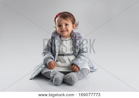 Portrait of a baby girl on a grey background