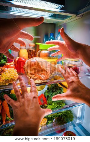 Human hands reaching for turkey leg food at night in the open refrigerator