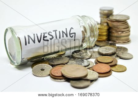 Investment Lable In A Glass Jar With Coins Spilling Out