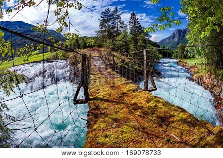 Suspension bridge over the mountain river. Beautiful Nature Norway natural landscape. Fisheye lens