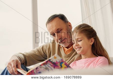 Joyful senior man is reading book for his small granddaughter. They are embracing and laughing