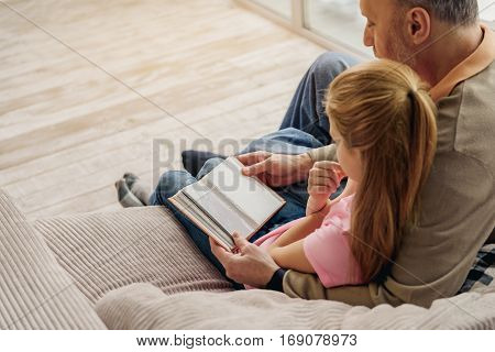 Cheerful grandfather is showing family album to his lovely granddaughter. They are sitting on sofa and embracing