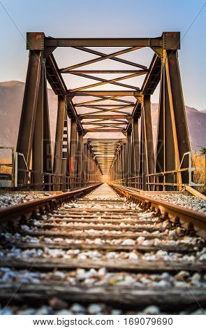 Old metal rail road bridge. With symmetrical metal structure and track.