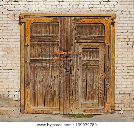 Old brown wooden gate with rusty handles and locks