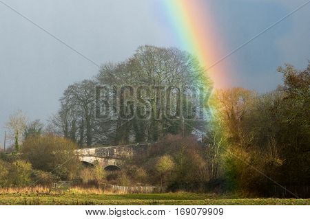 Railway bridge and rainbow, in countryside. Rural winter scene with bare trees around field outside Bath in Somerset UK