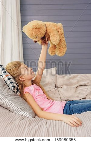 Happy girl is playing with her teddy bear at home. She is lying on sofa and laughing