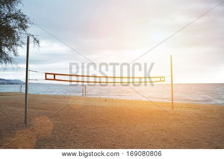 Sunrise above the empty beach and flares go through mounted volley grid stretched between two steel poles for playing sand volleyball, dramatic sky and blue ocean waters behind