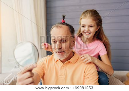I am very pretty man. Funny grandparent with female scrunchy on his hair is looking at mirror. His granddaughter is sitting behind him and laughing
