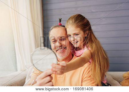 You look nice. Joyful grandfather and child are holding mirror and looking at it with joy. Laughing man has scrunchy on his hair