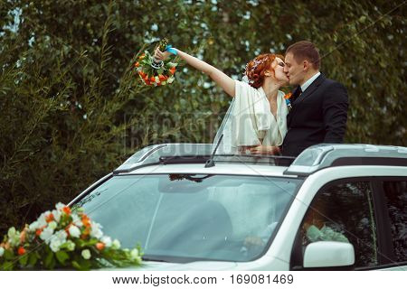 Just Married Kiss Standing In The Hatchway Of A Car